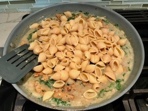 Shell pasta added to sauce in pan for Shell Pasta with Italian Sausage and Kale. It's loaded with a salty homemade Chicken Italian Sausage flavored with garlic and fennel in a parmesan, garlic and kale sauce.