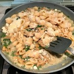 Mixing parmesan with pasta and Italian Sausage in pan for Shell Pasta with Italian Sausage and Kale. It's loaded with a salty homemade Chicken Italian Sausage flavored with garlic and fennel in a parmesan, garlic and kale sauce.