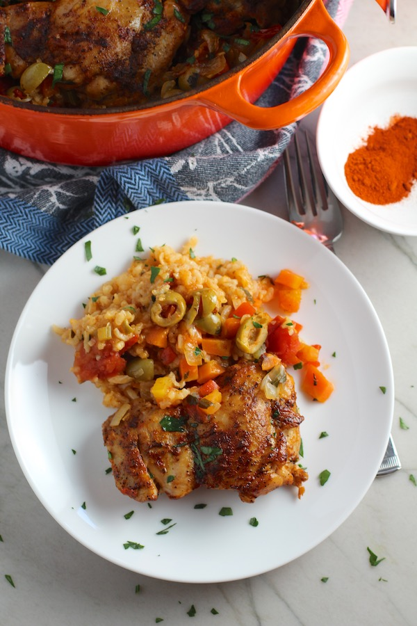Spanish Chicken and Rice on plate with fork.  It's hearty, smokey, and delicious! Paprika spice blend rubbed chicken thighs are seared then cooked with rice, onions, carrots, garlic, tomatoes, and olives for unbelievable flavor! #easydinners #chickenrecipes