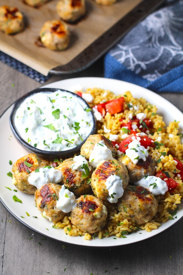 Ground Chicken Greek Meatballs on a plate with Tzatziki sauce over rice. Baked meatballs in back. These meatballs have garlic, feta, parsley, and oregano