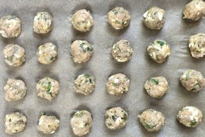 Raw Ground Chicken Greek Meatballs on a pan.  These meatballs have garlic, feta, parsley, and oregano