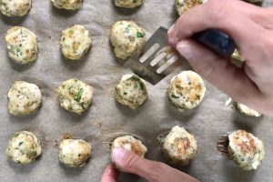 Flipping Ground Chicken Greek Meatballs on a pan. These meatballs have garlic, feta, parsley, and oregano
