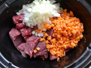 Raw beef cubes, diced onion, and diced carrots in pot for Shredded Beef Ragu Recipe with Pappardelle. It's so easy to make and has a thick meaty texture and a super rich delicious flavor.