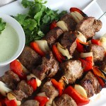 Garlic Steak Kabobs with red pepper and onion on platter with a Creamy Cilantro Sauce! #beefkabobs #steakkabobs