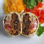Quinoa Black Bean Burritos cut in half and standing face up on plate. Packed with protein and fiber, but also cheese, tomato, cilantro, and sour cream!  The vegetarian 'meat' is taco-seasoned quinoa, black beans, and cauliflower.