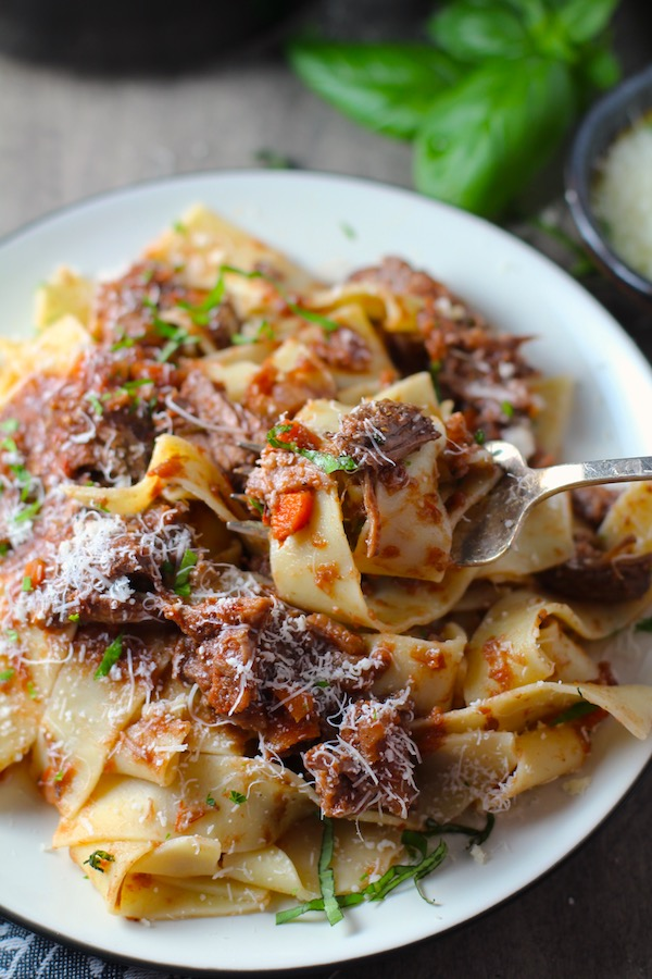 Shredded Beef Ragu Recipe with Pappardelle with a fork on plate with basil and parmesan on the table. It's so easy to make and has a thick meaty texture and a super rich delicious flavor.