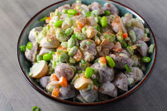 Red Potato Salad Recipe with Edamame and Harissa in a bowl on table. It's creamy, crunchy, meaty, tangy, peppery, salty, and oh, it's UNBELIEVABLE!