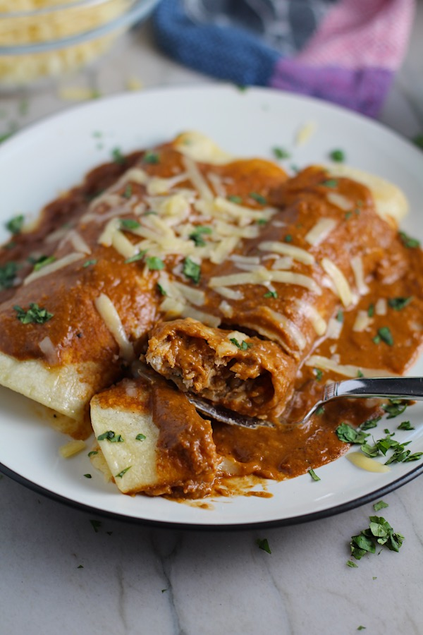 Fork with bite of Chicken Mole Enchiladas, on a plate with cheese and cilantro on top.  They are easy to make and delicious!  The Mole sauce has unsweetened chocolate, tomatoes, green chilis, garlic, adobo sauce, and spices blend harmoniously!