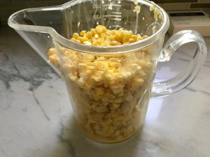 Fresh corn kernels in measuring cup for Creamy Corn and Blackened Chicken skillet dinner