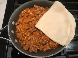 Beef mixture in skillet and pie crust being added to top for Empanada Beef Pie Recipe. It has a perfect flaky, buttery pastry on the outside with a savory, smokey, salty ground beef filling.  The best part is that everything cooks in one skillet!