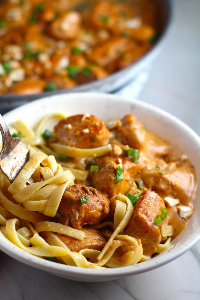 Quick Cooking Creamy Chicken Paprika in a bowl with pasta and fork scooping pasta and pan in background. It's creamy, smokey, rich, and hearty. This is an easy weeknight family dinner!