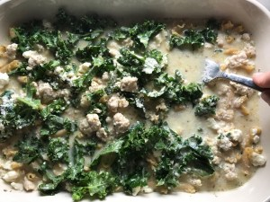 Fork pressing down dry pasta and kale into liquid with ground chicken and broth for Glorious Greek Ground Chicken Pasta Casserole. It has lean ground chicken with garlic, oregano, parmesan, feta and Kale.