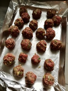 Raw meatballs on pan for Healthy Meatballs with Zucchini & Lean Beef. They're loaded with flavor from the garlic, minced onion, salt, and pepper.  The zucchini brings moisture, texture, and bulks up the meatballs with healthiness.