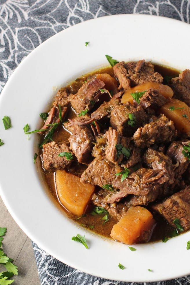 Slow Cooker Honey Garlic Beef and Potatoes in a bowl with parsley on top.  It's a delicious easy dinner with tender beef cubes are cooked in the slow cooker with lots of delicious garlic, onions, and potatoes.  Then honey and molasses are added for that touch of sweet.