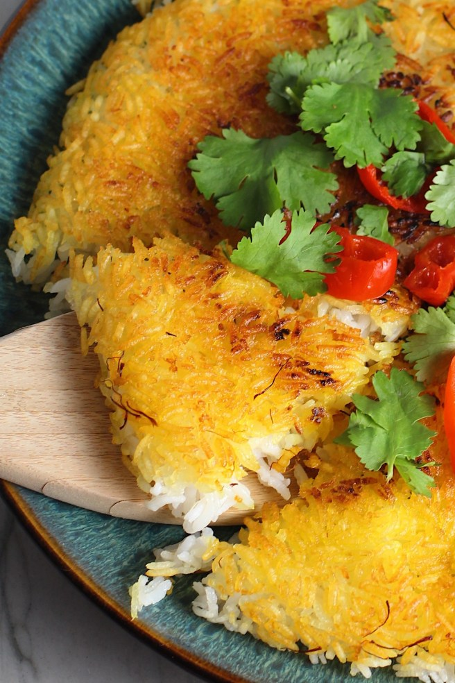 Saffron Butter Crispy Rice on a plate with cilantro and peppadew peppers on top.  Spatula scooping up a triangle piece. Saffron brings a floral note and beautiful yellow-orange color.  Added to the butter is what gives this crispy rice the buttery, crispy bottom.