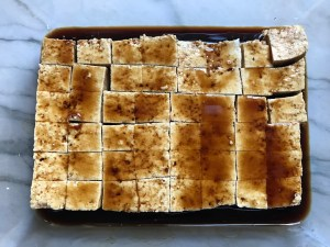 Firm tofu cut into cubes and marinating in teriyaki sauce for Thai Peanut Sauce Noodles with seared tofu and veggies.