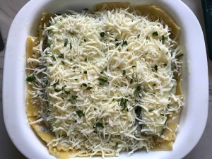 Shredded cheese and parsley on top of assembled White Lasagna Recipe with Zucchini and Ground Beef