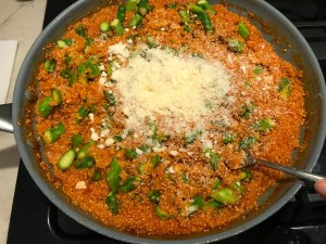 Parmesan cheese added to Asparagus and Tomato Quinoa Risotto in a pan.