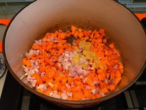 Diced carrots, onions, garlic, and ginger cooking in pot for Golden Carrot Ginger Soup Recipe.
