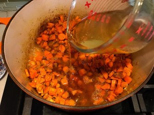 Broth being poured into carrots and onions cooking in pot for Golden Carrot Ginger Soup Recipe.