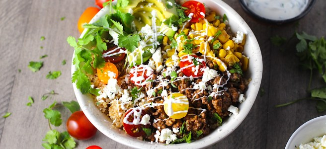 Taco Quinoa Bowl with Ground Beef, corn, cotija cheese, tomatoes, fresh cilantro, and cilantro lime crema drizzled on top. Bowl of crema, bowl of cotija cheese, tomatoes and cilantro on the table.
