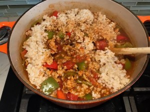Mixing cooked rice into pot with ground chicken cooking, peppers, and tomatoes for Tex Mex Unstuffed Peppers with Ground Chicken.  Juicy Sweet Bell Peppers are chopped up and cooked with the Tex Mex style ground chicken, tomatoes, Mexican seasonings, cheese, rice and corn tortillas.
