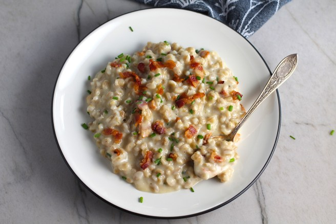 Velvety Barley Recipe with Bacon and Gruyere Cheese on plate with crispy bacon bits and diced chives on top and spoon with scoop on side of plate. It's creamy, rich, nutty, smokey, hearty, and utterly delicious.