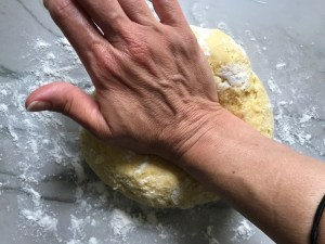 Hand kneading dough on floured counter for Easy Homemade Pasta recipe.