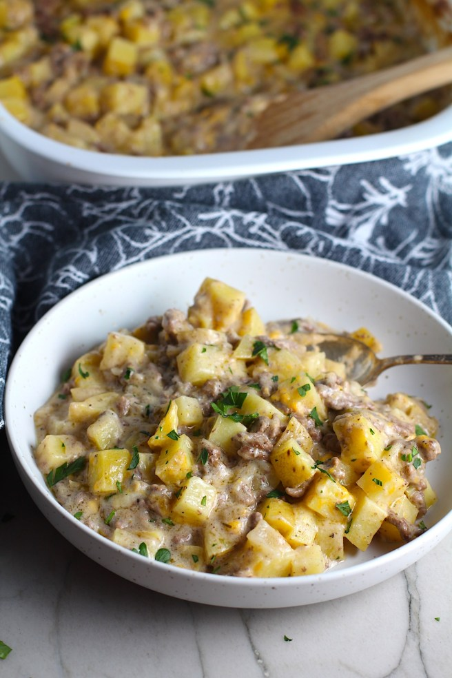 Cheesy Hamburger Potato Casserole in a bowl with a spoon and casserole in background. It's an easy, yummy, and cozy weeknight family dinner.