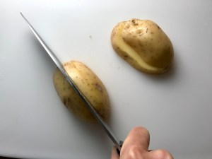 Knife slicing raw yukon gold potato with skin on for Cheesy Hamburger Potato Casserole. It's an easy, yummy, and cozy weeknight family dinner.