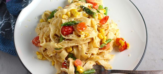 Fresh, Creamy Pasta Primavera Recipe on a plate with fork on counter. It has fettuccine, parmesan cheese, roasted asparagus, carrots, tomatoes and fresh corn kernels.
