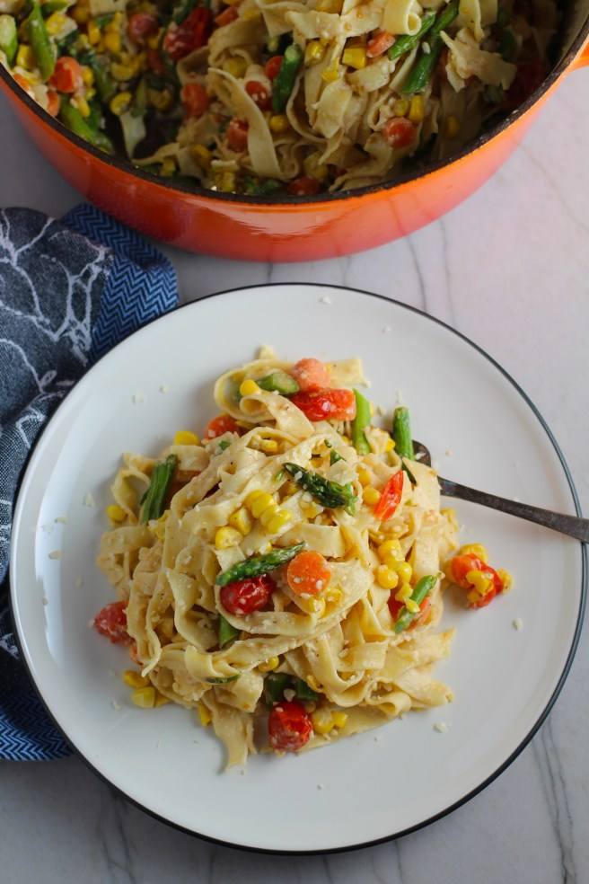 Fresh, Creamy Pasta Primavera Recipe on a plate with fork and pot in background on counter. It has fettuccine, parmesan cheese, roasted asparagus, carrots, tomatoes and fresh corn kernels.