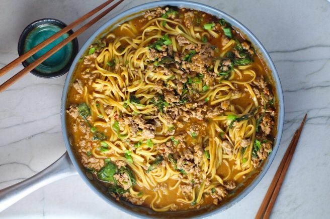 Dan Dan Noodle Recipe with Ground Chicken and scallions in a pan on counter with chopsticks next to it.