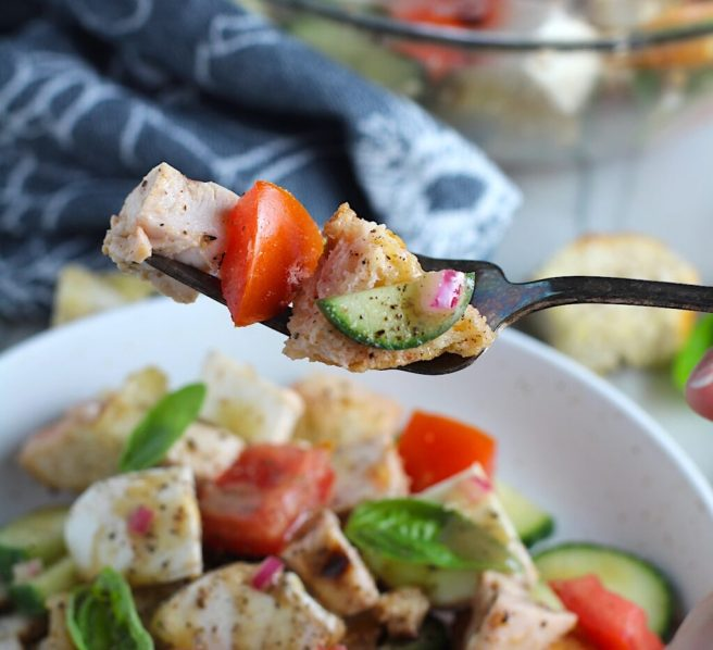 Toasted bread cubes, chicken, tomatoes, cucumber on a fork over a bowl of Chicken Panzanella Salad Recipe. It's absolutely delicious.