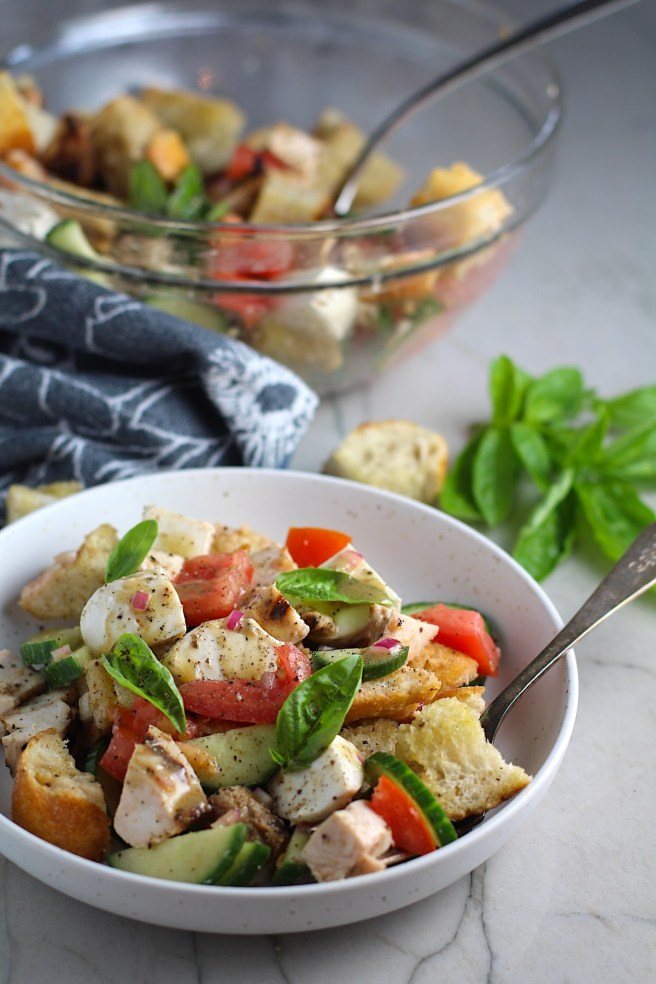 Chicken Panzanella Salad Recipe in a bowl with fork.  It has Toasted bread cubes, chicken, tomatoes, cucumber, basil, and mozzarella.  Serving bowl in back