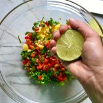 Hand squeezing lime half over bowl of diced mango, red pepper, scallions, jalapeno, and cilantro for Grilled Shrimp Tacos