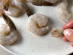 Tail removed from a raw shrimp with more shrimp on the plate for Grilled Shrimp Tacos