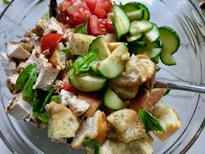Toasted bread cubes, chicken, tomatoes, cucumber, and basil in a bowl for this Chicken Panzanella Salad Recipe with fresh garden veggies is absolutely delicious.