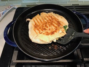 Spinach Artichoke Chicken Stuffed Pita grilling on a round grill pan on the stove.