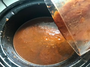 Birria Taco Sauce being poured from the blender to the slow cooker for Birria Tacos. This Birria Tacos Recipe in the Slow Cooker has shredded beef and Oaxaca cheese melted together in corn tortillas in a pan.