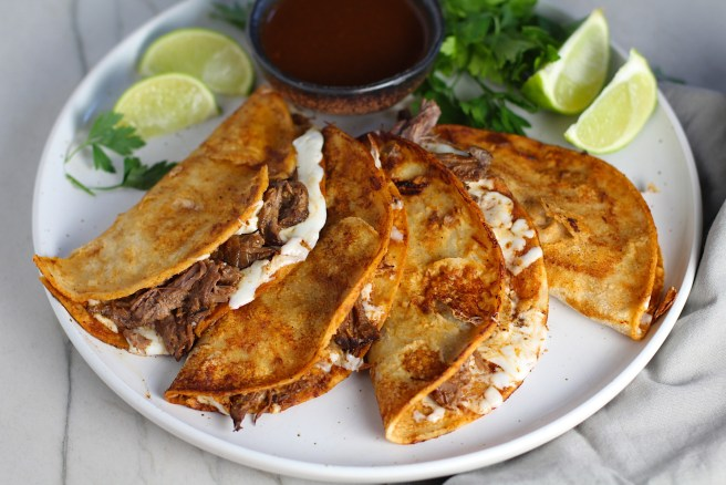 Four tacos fanned out on a plate for this Birria Tacos Recipe. Each taco has shredded beef and oaxaca cheese oozing out. On the plate is a bowl of red sauce, lime wedges, and cilantro.