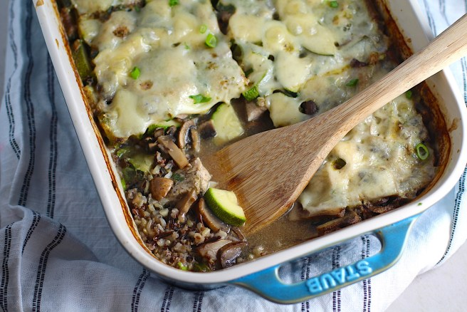 Chicken Wild Rice Casserole with Zucchini and Mushrooms in a casserole dish with missing corner piece and wood spatula in dish.