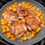 Seared chicken thighs, butternut squash cubes and shallots cooking in a frying pan for Crispy Sage Chicken, Butternut Squash, and Shallots.