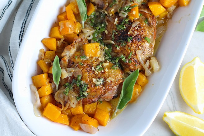 Crispy Sage Chicken, Butternut Squash, and Shallots on a platter with fresh sage leaves and topped with a buttery garlic, lemon, sage sauce. Lemon wedges, fresh sage leaves, and a kitchen towel on counter.