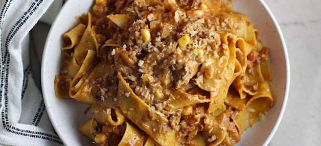 Southwestern Pasta with Ground Beef and Corn and breadcrumbs on top on a plate with fork holding a bite. The sauce is thick and hearty with ground beef, sweet corn kernels, chunky tomatoes, chipotle peppers in adobo, green chiles, parmesan cheese, and lots of smokey and spicy seasonings.