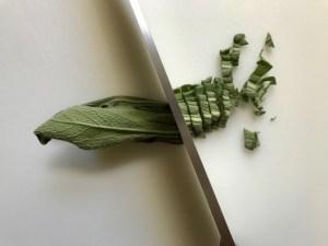 Knife slicing fresh sage leaves for Sage Butter Potatoes.