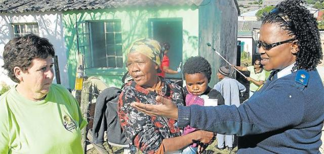 WOMEN AT WORK: Woman's Network members Lieutenant-Colonel Nosipho Nodwala, right, and Warrant Officer Joy van de Merwe, left, with Station Hill resident Mary Booysen and her two-year-old daughter Ashante