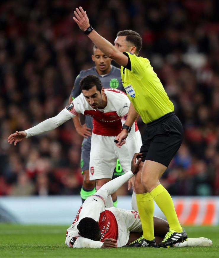 The referee hurries on the medical staff as the severity of Welbeck's injury is quickly established