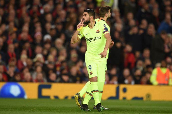 Suarez celebrates in front of the Stretford End