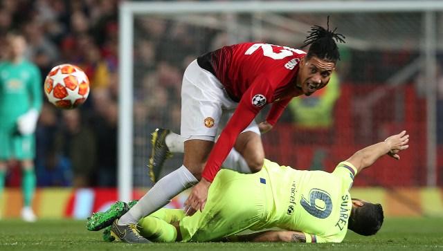 Luis Suarez lies in a heap after Smalling's challenge